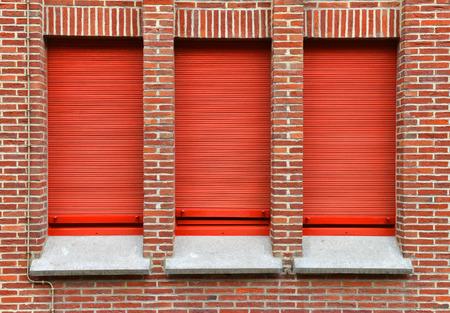 trois fenêtres avec volet roulant rouge