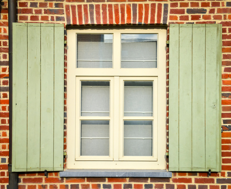 red shutters: window with green shutters on red brick wall