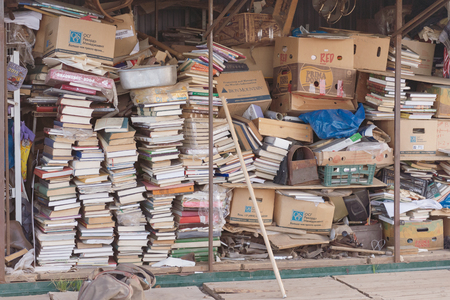 Flea market. Sale of old things. Stacks of old books. Shed with books. Editorial