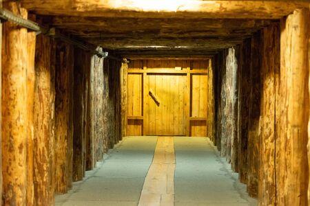 Salt caves near Krakow. Underground corridor with vestibule door. Wooden support beams.