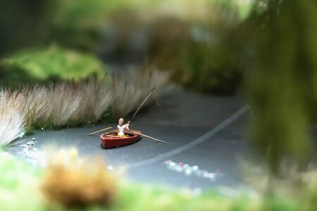 Model of a pond with a boat and a fisherman. A fisherman catches a fish. 免版税图像
