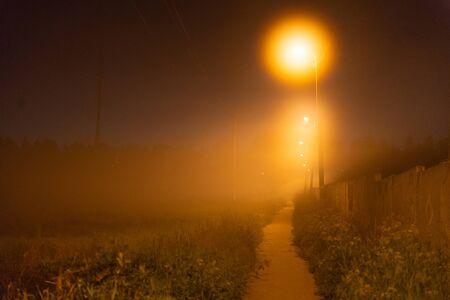 Night path under the light of lanterns. Night fog and street lights. Foto de archivo