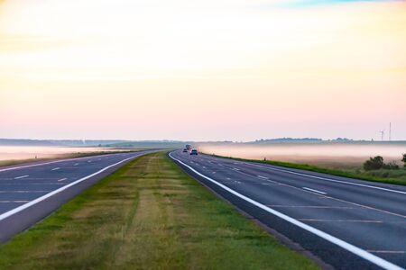 Morgen vor Sonnenaufgang. Die lange Autobahn geht in die Ferne. Neblige Felder am Straßenrand.