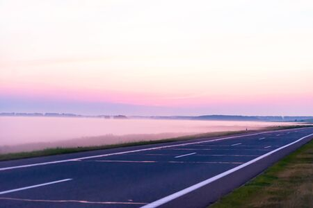 Morning before sunrise. Misty fields at the edge of the road. A multicolored sky and a sea of mist beneath it.