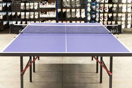 Tennis table. Sports accessories shop. Tennis table on the background of shelves with goods.