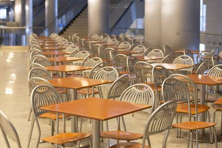 A long row of tables from the cafeteria in the lobby of the building. Furniture for cafes. Crocus-Expo. Archivio Fotografico