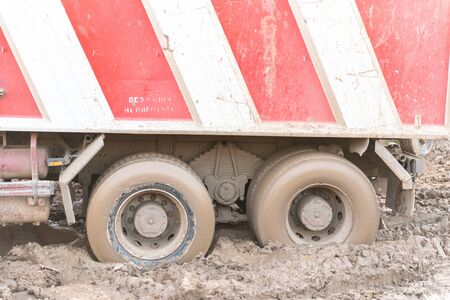 Stuck truck. The rear wheels are muddy. Blurred primer.