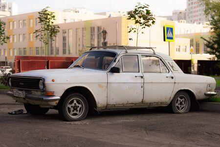 Old Soviet car. Mark-Volga. A rusty car parked on flat wheels.