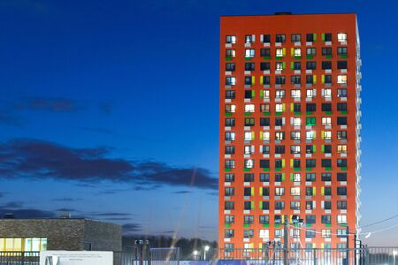 New multi-storey building. Red apartment building. Glowing Windows in the darkening sky.