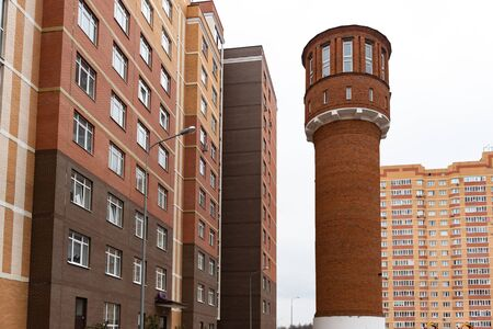 Water tower. Historical heritage in the city. Old buildings among high-rise buildings.