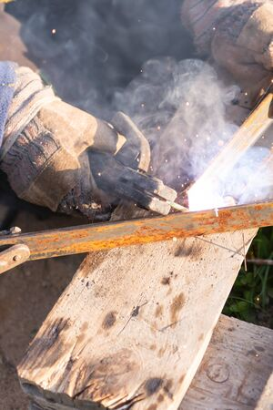 Welding iron. The worker welds the iron parts. Workplace on a pallet with tools.