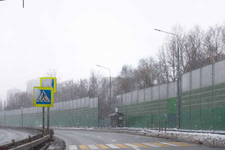 Pedestrian crossing on the highway. Snowfall on the road, photos from the car