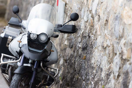 Off-road motorcycle at the stone wall. A gray motorcycle is leaning against the wall.