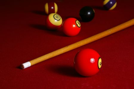 A pool cue and balls rest on a red felt table