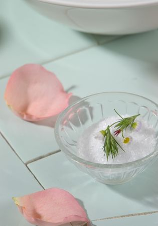 A bowl of bath salts with herbs over a soothing green tile backdrop. photo