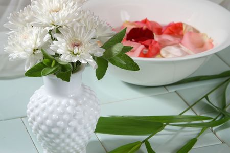 hobnail: A vase of white mums stands before a rose petal bath.