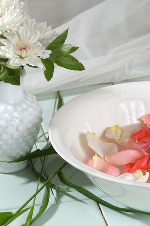 destress: A vase of white mums sits beside a rose bath. Stock Photo