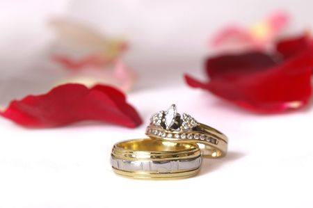 high-key wedding bands on pure white background with rose petals Stock Photo