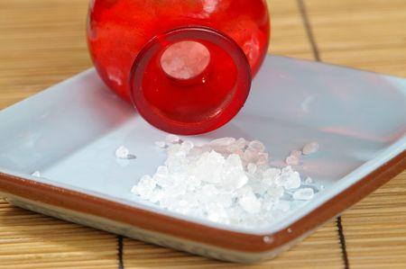 salts: Bath salts spill from a bright red jar.