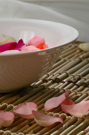Rose petals float in a bowl. Spa-like setting.