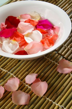 destress: Bowl of rose petals on bamboo spa mats. Stock Photo