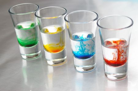 Strings of liquid color merge into water.