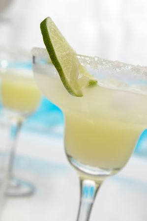 A thin lime slice in a margarita. Selective focus on edge of lime.