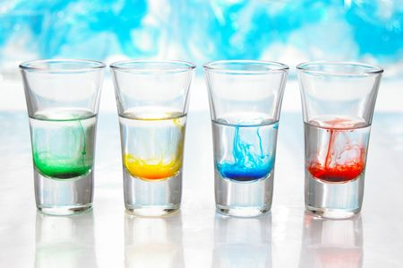 Swirls of bright color mix with water in clear glass vials.