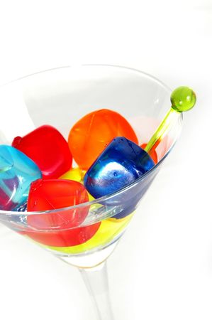 A martini with colored ice cubes, high key.