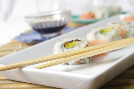 soysauce: Sushi served on a contemporary plate over a traditional bamboo mat.
