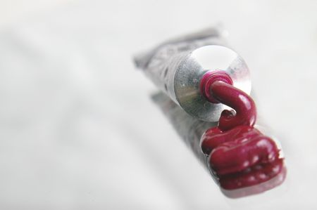 Lipgloss oozes from a silver tube. Focus is on tube opening.