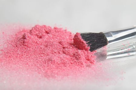 Pink sparkle eye shadow powder with an applicator brush.