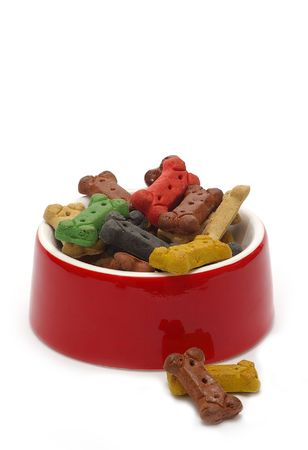 A bright red bowl brimming with bone-shaped dog treats. Stock Photo - 1007587