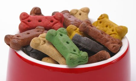 A brimming bowl of assorted dog bones over white background. photo