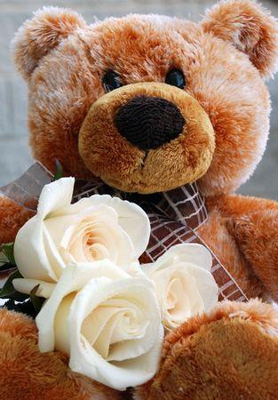 Brown teddy bear holding three white roses