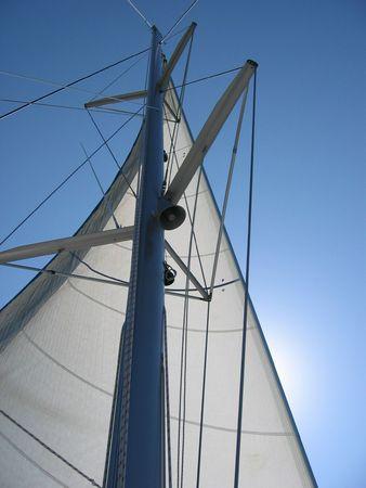 sun lit: White sail against sun lit blue sky Stock Photo
