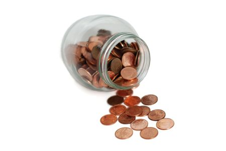 Pennies spilling out of a clear jar  Stock Photo