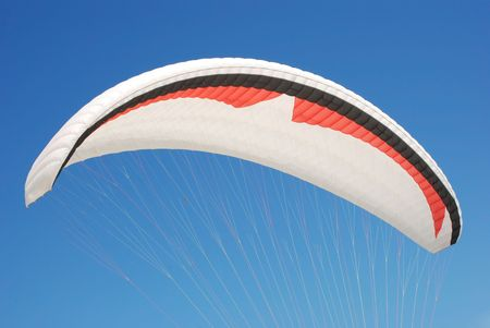 Paragliding sport. Close up of parachute against blue sky.