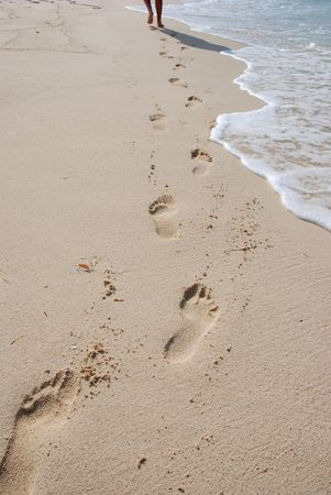 Walking on beach. Footprints on sand Stock Photo