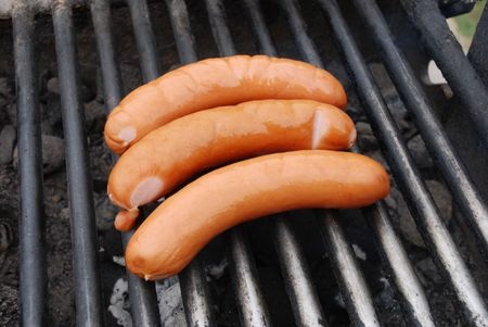 Cooking sausages on outdoor barbecue