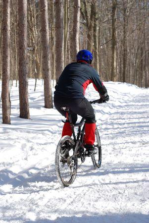 road bike: Snow biker in winter forest.