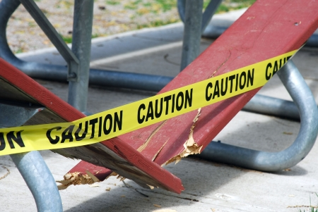 Caution tape on a broken wooden bench