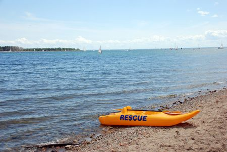 Yellow rescue boat on the lake beach photo