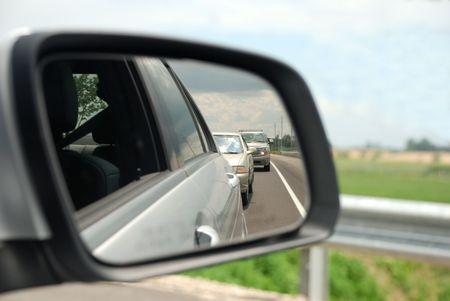 rear view mirror: Cristal del espejo retrovisor que refleja una l�nea de coches detr�s de