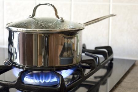Stainless steel pot on a gas stove Standard-Bild