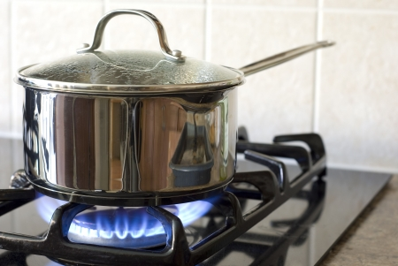 burner: Stainless steel pot on a gas stove Stock Photo