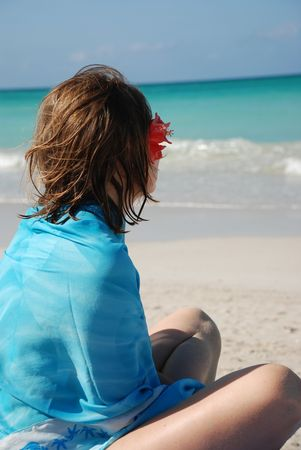 Girl with flower in hair dreaming on a beach photo