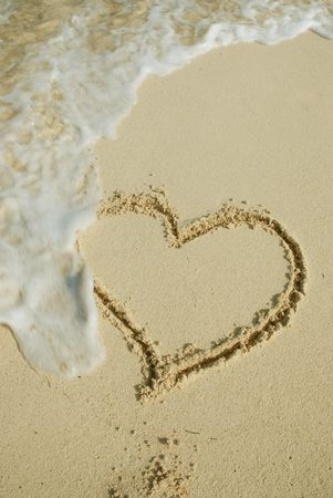 Heart on sand beach being washed away