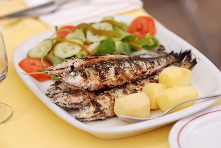 Grilled sardine with potato and salad photo
