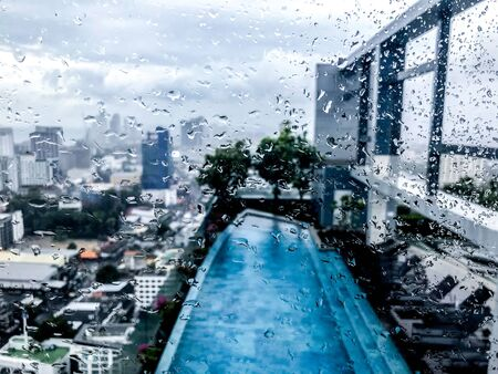 view at the swimming pool on high floor of a building through window at a rainy day. There are rain drops on the window. City view. Blurred background.